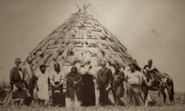 A traditional Wichita grass house; photograph from a postcard ca. 1900-1910; used by permission of the Anadarko Heritage Museum.